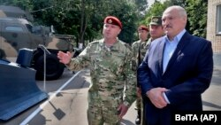 Belarusian President Alyaksandr Lukashenka (right) inspects police vehicles as he visits the Interior Ministry special forces base in Minsk on July 28.
