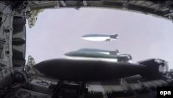 На кадре из видео, опубликованном на сайте министерства обороны России, — сброс снарядов с бомбардировщика Ту-22М3 предположительно над сирийским городом Дэйр аль-Заур.