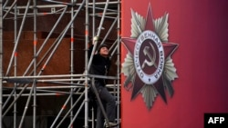 Russian worker installs a banner for the upcoming Victory Day celebrations on Moscow's Red Square, April 27