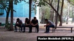 Студенты сидят на скамейке во дворе общежития в Алматы. Иллюстративное фото.
