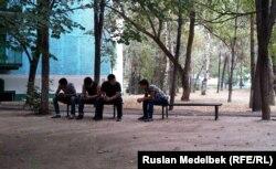 Жатақхана алдында отырған студенттер. (Көрнекі сурет)