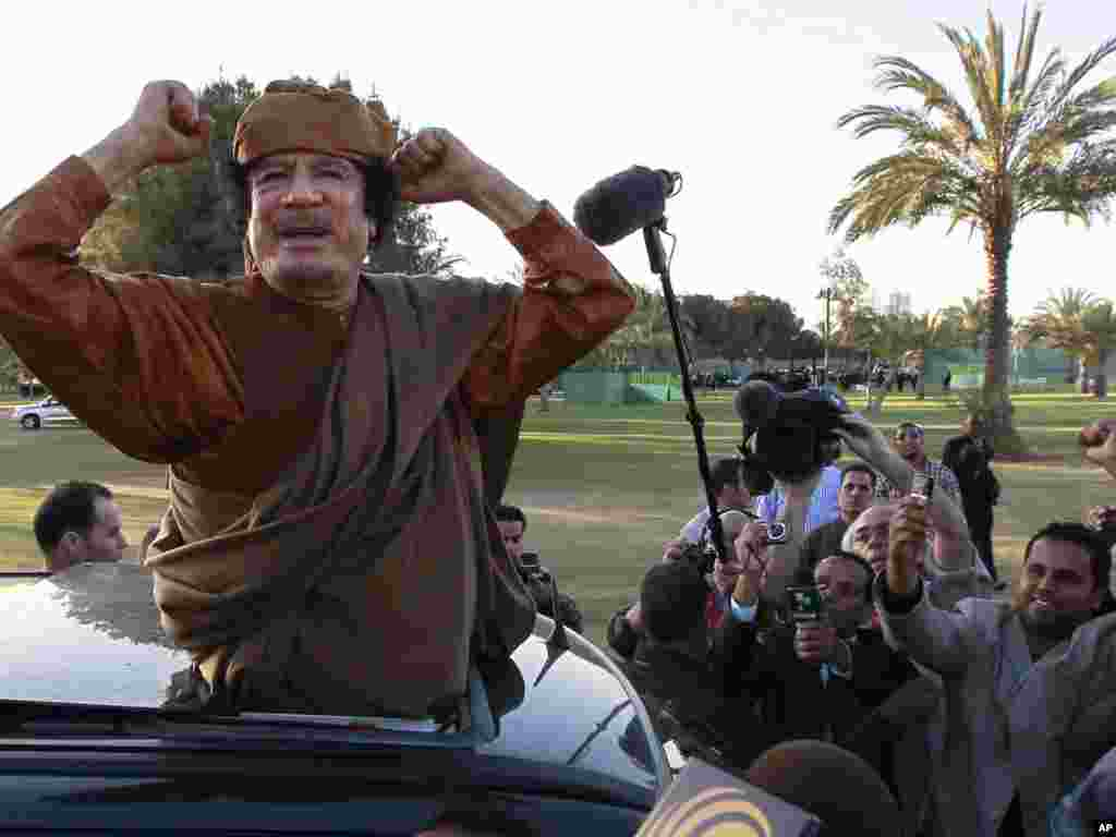 "Qaddafi gestures to his supporters in Tripoli on April 10, 2011. Libyan state television aired an audio message from Qaddafi urging loyalists to take arms and fight ""traitors and NATO."""