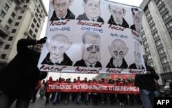 Участники акции протеста с карикатурами на российских лидеров. Москва, 7 ноября 2011 года.