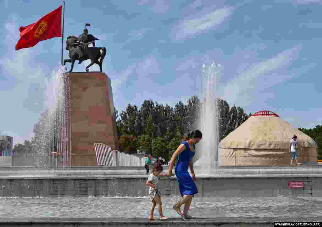 A Kyrgyz woman and a girl cool off by a fountain in Bishkek.
