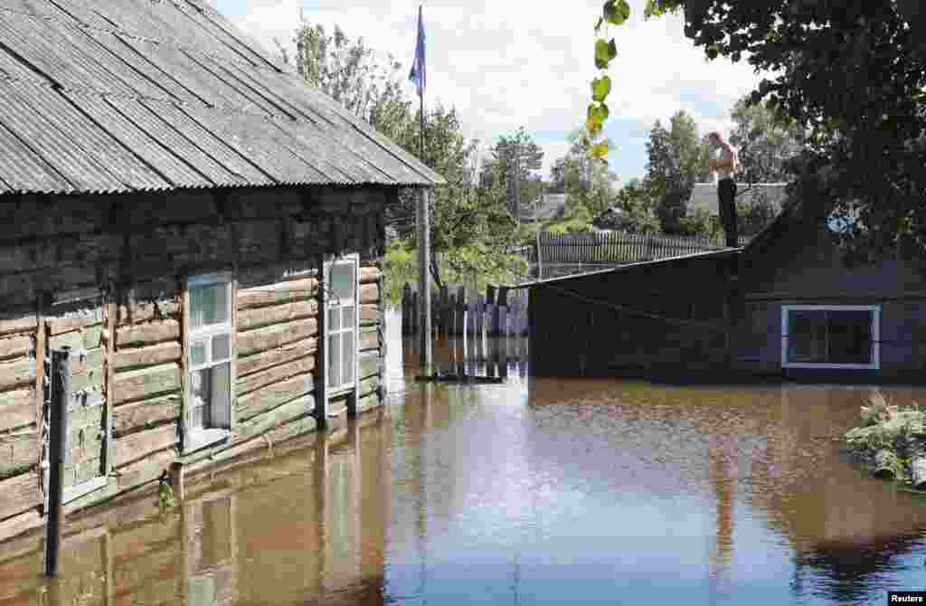 A local resident stands on the roof of a building in the flooded settlement of Krasnaya Rechka on the outskirts of the Far Eastern city of Khabarovsk, Russia. (Reuters/Vladimir Barsukov)