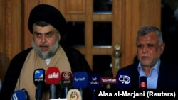 Iraqi Shi'ite cleric Moqtada al-Sadr speaks during a news conference with Leader of the Conquest Coalition and the Iran-backed Shi'ite militia Badr Organisation Hadi al-Amiri, in Najaf, Iraq June 12, 2018