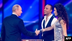 Russian Prime Minister Vladimir Putin (left) shakes hands with Azerbaijan's entry in the 2009 Eurovision contest, AySel and Arash, during rehearals in Moscow.