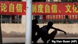 """Đaci ispred jedne od srednjih škola na zapadu Kine gde živi ujgursko stanovništvo ispred plakata na kojem piše """"Samopouzdanje u sistem, samopouzdanje u kulturu"""""""