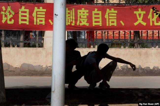 """Коммунистическая символика и пропаганда окружает жителей Синьцзяна постоянно (как и всех остальных китайцев). Студенты у входа в одну из областных школ. Лозунги гласят: """"Постоянный самоконтроль! Постоянный культурный контроль!"""""""