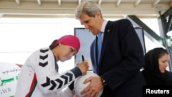 Zahra Mahmoodi (left), captain of the Afghan women's national soccer team, signs an Afghan-made soccer ball for U.S. Secretary of State John Kerry at the U.S. Embassy in Kabul last year.