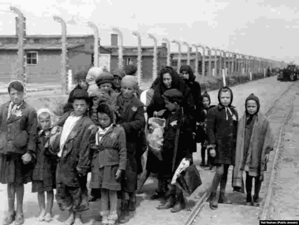 На фото слева: 1944 год. Женщина с детьми направляется в газовую камеру. На заднем фоне видны деревянные бараки – это лагеря Биркенау, дополнительно построенные в Освенциме. После войны здания были разрушены, но кирпичные стены и дымоходы сохранились.