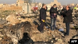 TV journalists stand amid the wreckage after a Ukrainian plane crashed in Iran, possibly downed by a missile.