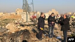 TV journalists stand amid the wreckage of the Ukrainian plane, which was carrying 176 passengers, on January 8.