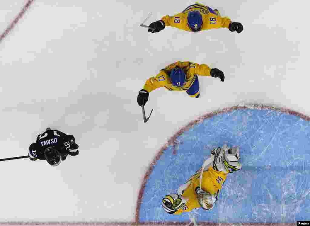 Sweden's goalie Valentina Wallner (bottom) celebrates with teammates Linnea Backman and Anna Borgqvist (top) next to Japan's Chiho Osawa (left), after winning their women's preliminary-round hockey game.