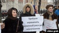 Ипотечники стоят в Москве с плакатом, требующим ограничить валютный риск для ипотечников.