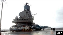 A file photo of the Russian aircraft carrier, the Admiral Kuznetsov, docked in the Syrian port of Tartus, where Moscow will now be expanding operations.