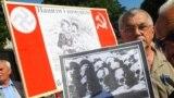 Учасник мітингу-реквієму тримає фото черепів та тлі плаката із зображенням Сталіна та Гітлера в день пам'яті жертв комуністичного і нацистського режимів. Львів, 22 червня 2011 року