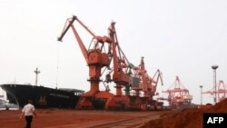 Bulldozers scoop soil containing various rare-earth elements to be loaded onto a ship at the port in Lianyungang, in China's eastern Jiangsu Province, for export to Japan.