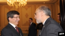 Iranian Foreign Minister Ali Akbar Salehi (right) shakes hand with his Turkish counterpart Ahmet Davutoglu in Istanbul last month.