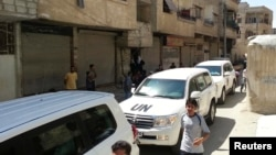 Residents gather around a convoy of UN vehicles carrying a team of UN chemical-weapons experts at one of the sites of an alleged poison-gas attack in the southwestern Damascus suburb of Mouadamiya on August 26.