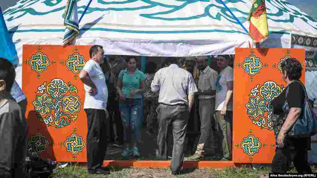 Люди заходят посмотреть в один из павильонов ярмарки