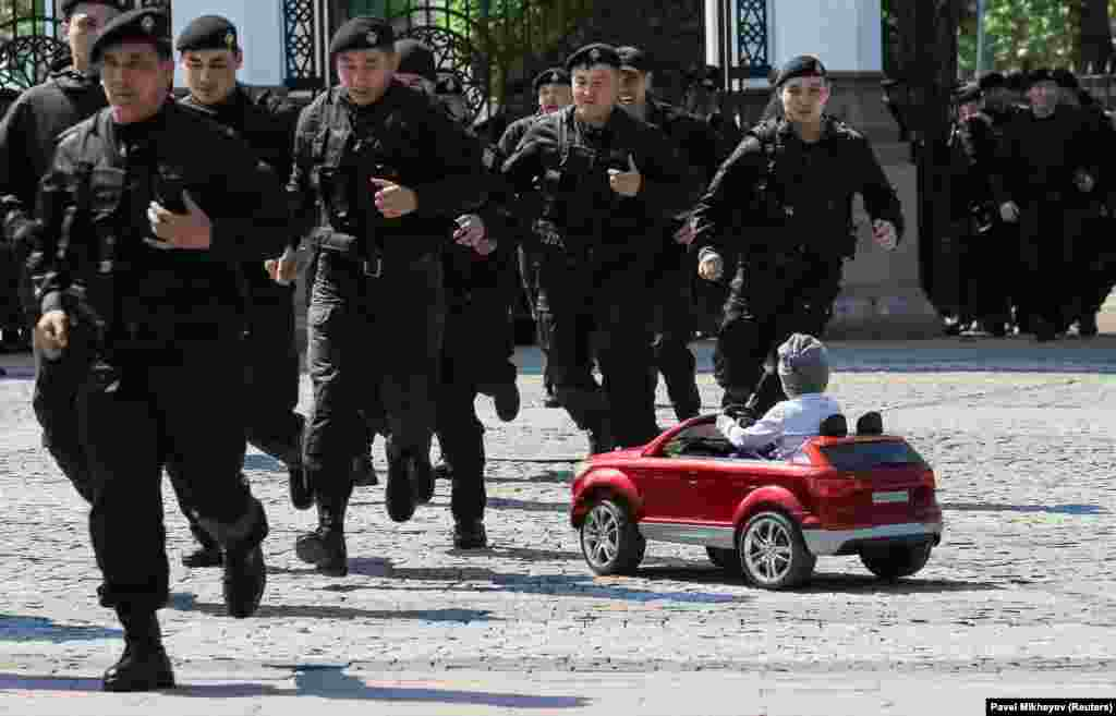 A child looks on as Kazakh police officers run to detain antigovernment protesters during a rally in Almaty on May 1. (Reuters/Pavel Mikheyev)