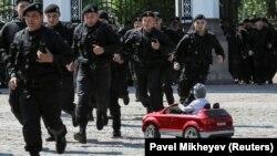 Бойцы спецназа вбегают в Центральный парк отдыха в Алматы, где проходит несанкционированный митинг, 1 мая 2019 года.