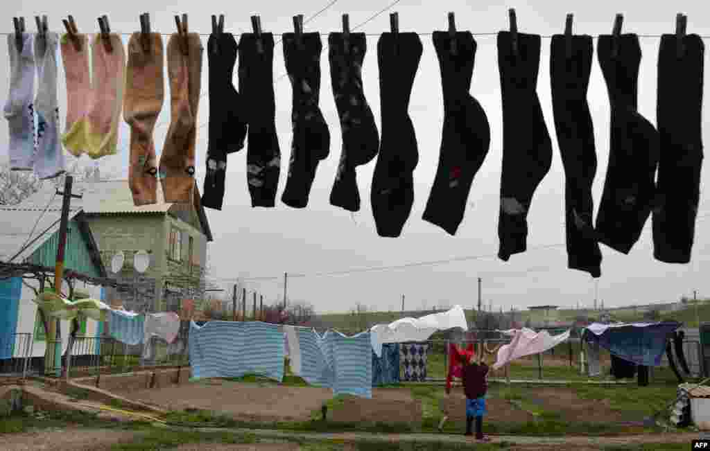 "A woman hangs wash near her home in the Ukrainian village of Berdyanske, some 4 kilometers west of Shyrokyne, near Mariupol, where the use of heavy weapons has been reported. The French, German, Russian, and Ukranian foreign ministers expressed ""grave concern"" on April 14 about violations of a shaky cease-fire in separatist-held east Ukraine but pledged to continue dialogue. (AFP/Genya Savilov)"
