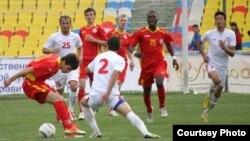 Кыргызстандын улуттук курамасынын (кызыл кийимчен) футболчулары Тажикстандын улуттук курамасы менен беттешүүдө.