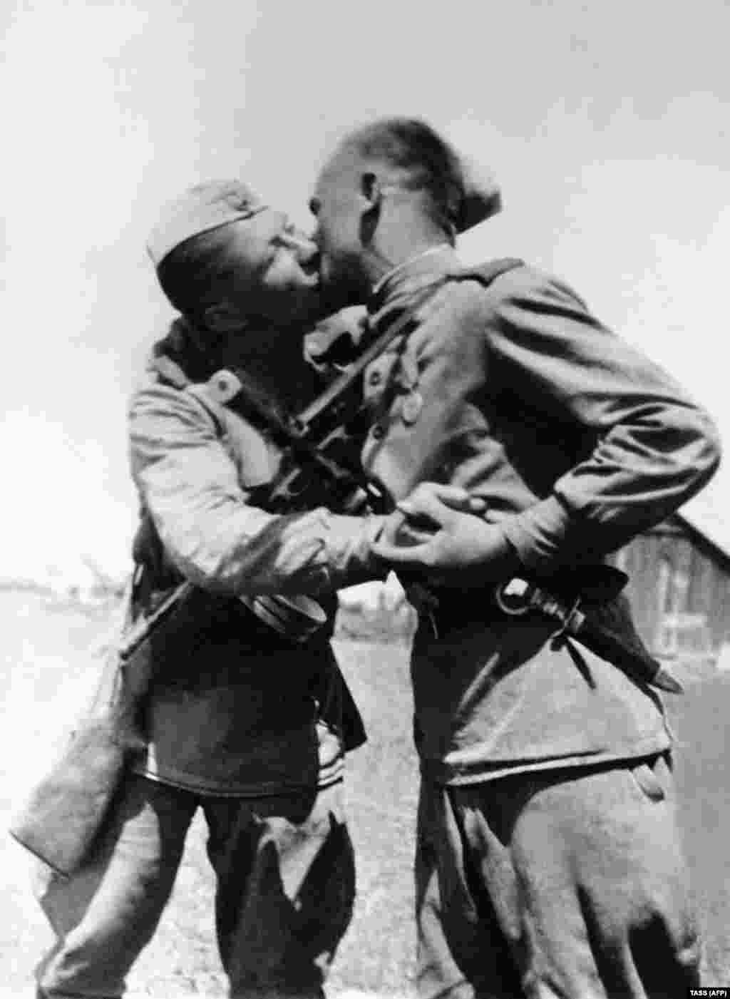 "Red Army soldiers kiss after victory was declared over Nazi Germany. The ""socialist fraternal kiss"" was reportedly an expression of equality -- upturning the ancien regime's custom of lowly subjects kissing noble hands (or feet, in ancient Rome and Persia)."
