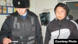 Полицейский с задержанным Наурызбеком Байшолаковым. Актобе, 24 ноября 2013 года.