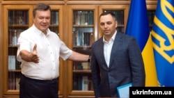 Ukrainian ex-President Viktor Yanukovych (left) and aide Andriy Portnov talk in Crimea in August 2010.