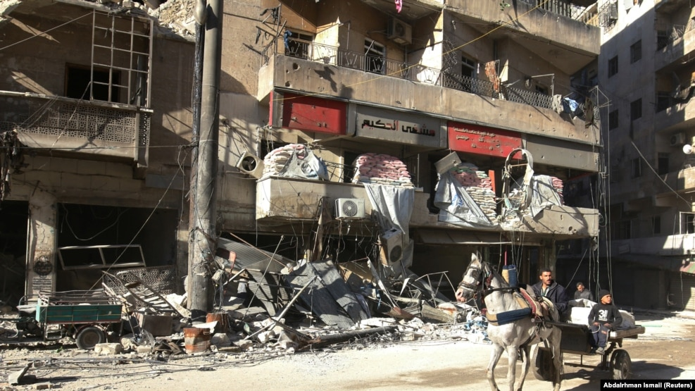 People ride a cart pulled by a horse near the damaged Hakim hospital, in the rebel-held besieged area of Aleppo.