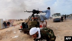 Libyan rebel fighters try to defend a gate of the north-central key Libyan oil town of Ras Lanuf as Muammar Qaddafi's loyalist forces approach their positions on March 10.