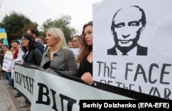 Ukrainian activists hold up anti-Russian and ant-Putin placards and banners as they join a protest in front of Russian Embassy in Kyiv last month.
