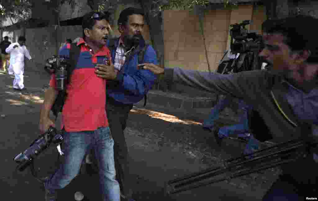 Asif Hassan (left), a photographer for French news agency Agence France-Press (AFP), is helped by a fellow photographer after Hassan was shot during a protest in Karachi, Pakistan, against satirical French weekly Charlie Hebdo. (REUTERS/Akhtar Soomro)