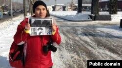 Блогер Нурали Айтеленов держит плакат рядом с рестораном, где прошла встреча акима Алматы с некоторыми блогерами. Алматы, 5 февраля 2014 года.