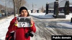 Блогер Нурали Айтеленов, не приглашенный на встречу с акимом Алматы, держит плакат рядом с рестораном, где обедают градоначальник и блоегры. Алматы, 5 февраля 2014 года.