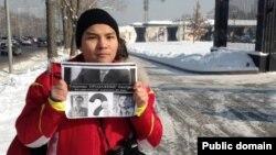 Блогер Нурали Айтеленов держит плакат рядом с рестораном, где аким Алматы Ахметжан Есимов принимает других блогеров-активистов казахстанского Интернета. Алматы, 5 февраля 2014 года.