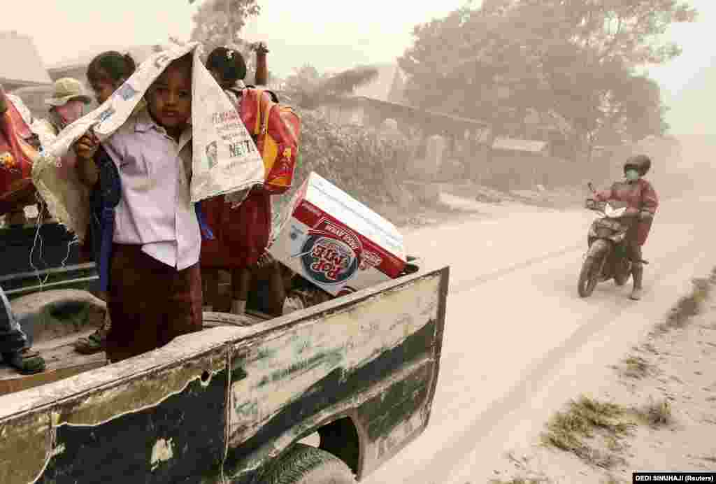 Indonesian students take cover from volcanic ash falling from Mt. Sinabung as they ride on a pickup truck and a motorcycle after the volcano erupted at Beganding village in Karo, North Sumatra, Indonesia Province. Mt. Sinabung is one of the most active volcanos in Indonesia. The 2,460-meter volcano had been dormant for 400 years before it erupted in August 2010. (epa/Dedi Sinuhaji)