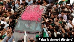 Supporters of former Pakistani Prime Minister Nawaz Sharif crowd around his car as his convoy enters Rawalpindi on August 9.