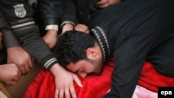An Iraqi man weeps over the body of a relative killed in a bomb attack in Ramadi on December 30.