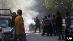 Iranian protesters gather next to a garbage container that was set on fire during scuffles with police in central Tehran, near the main bazaar,on October 3.