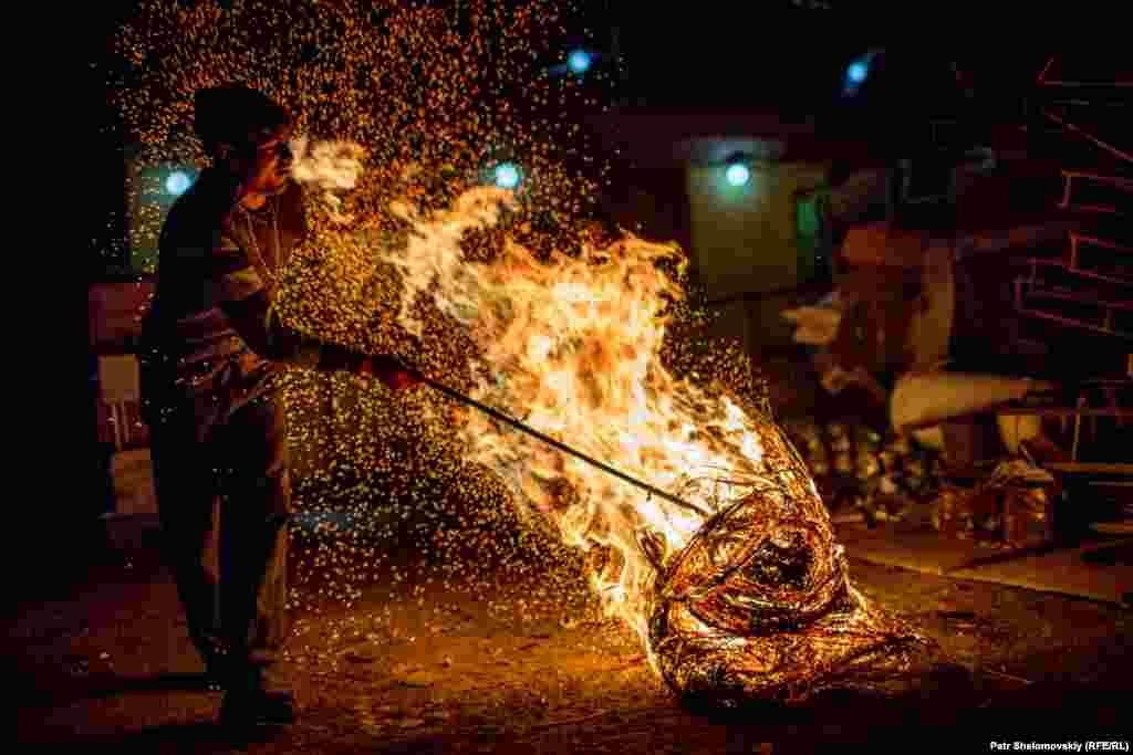Raush, a refugee from Nagorno-Karabakh, burns cables at a scrap metal shop.