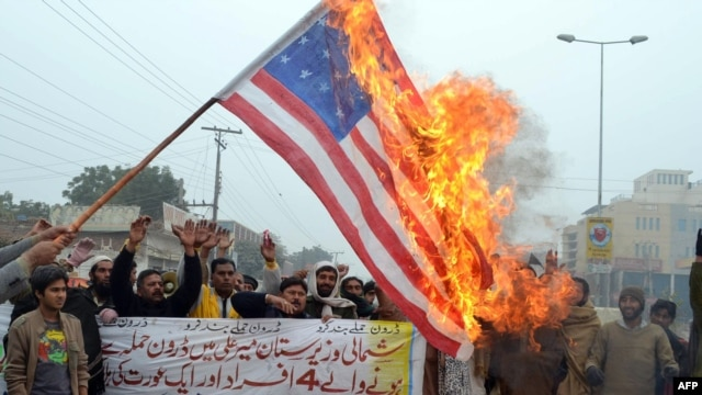 Pakistani demonstrators shout slogans beside a burning U.S. flag during a protest against drone strikes in Multan on January 3.