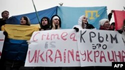 "Demonstrators hold placards reading ""Crimea is Ukraine"" during a rally on Independence Square in central Kyiv in March."