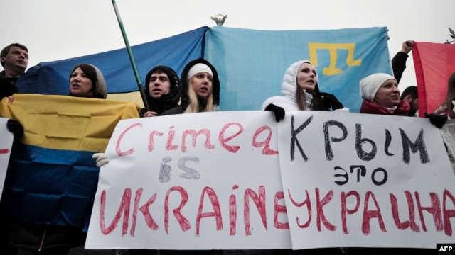 "People hold signs reading ""Crimea is Ukraine"" during a rally on Independence Square in central Kyiv on March 1."