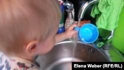 Ребенок моет кружку водой из-под крана. Темиртау, 21 мая 2015 года.