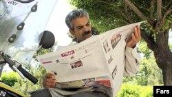 Iran, Tehran -- A man reads a newspaper