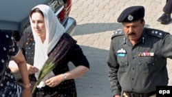 A police officer escorts Benazir Bhutto (left) as she visits a national shrine in Karachi in October 2007.